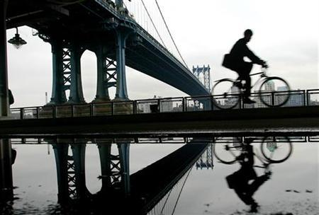 A silhouetted man rides his bike past the Manhattan Bridge in New York, November 20, 2004. REUTERS/Shannon Stapleton