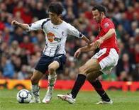 <p>Ryan Giggs, do Manchester United, disputa bola com Lee, do Bolton Wanderers, em partida do Campeonato Inglês. A vitória em casa do United por 2 x 1 sobre o Bolton o colocou na liderança do torneio. REUTERS/Phil Noble</p>