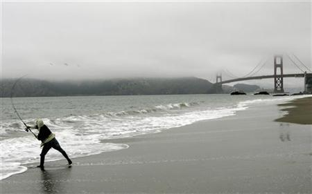 A man casts his fishing line into the Pacific Ocean along Baker Beach with the Golden Gate Bridge in background in San Francisco, California May 27, 2007. REUTERS/Robert Galbraith