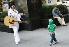 """<p>Человек, одетый как Элвис Пресли, показывает на маленького мальчика в Нью-Йорке 5 октября 2009 года. Прядь волос Элвиса Пресли, упавшая с его головы, предположительно, в 1958 году, когда """"король рок-н-ролла"""" был призван в армию США, ушла в воскресенье с молотка за $18.300, сообщили представители аукционного дома Leslie Hindman в Чикаго. REUTERS/Mike Segar</p>"""