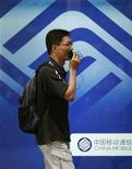 <p>Un hombre habla por celular mientras camine frente del logo de China Mobile en Hong Kong, 20 oct 2009. China Mobile reportó el martes un aumento de un 2,8 por ciento de sus ganancias del tercer trimestre, pero el resultado no cumplió con las expectativas por crecientes costos en el desarrollo de la red de tercera generación (3G) y una competencia cada vez más intensa. REUTERS/Bobby Yip</p>