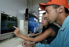 <p>Imagen de archivo en que una empleada de gobierno enseña a un hombre usar internet, en la ex colonia de esclavos Ivaporunduva, al sur de Sao Paulo, 2 mayo 2005. Brasil presentará en noviembre un plan para extender el acceso a internet de banda ancha a todo el país que demandará una inversión de 10.000 millones de reales (5.740 millones de dólares), dijo el martes a Reuters el ministro de Comunicaciones. Helio Costa dijo en una entrevista que él apoyo un esquema de asociación pública-privada para realizar el plan, que promete acercar internet de banda ancha a lo ancho del país en cinco años. REUTERS/Rickey Rogers/archivo</p>