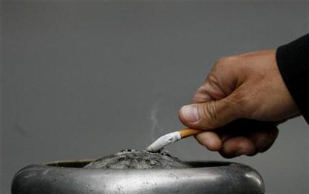 A man extinguishes his cigarette in central Sydney May 11, 2009. REUTERS/Daniel Munoz