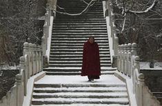 <p>Тибетский монах спускается по заснеженной лестнице в монастыре Кумбун в провинции Цинхай, Китай 11 марта 2009 года. 21 октября 1950 года Китай начал оккупацию Тибета. REUTERS/David Gray</p>