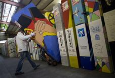 <p>A worker moves a domino pieces that symbolises a segment of the Berlin Wall in a warehouse in Berlin October 21, 2009. REUTERS/Thomas Peter</p>