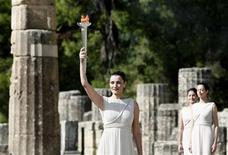 <p>Греческая актриса Мария Нафплиоту поднимает над головой факел с Олимпийским огнем в Древней Олимпии 22 октября 2009 года. Эстафета Олимпийского огня зимних Игр 2010 года стартовала в четверг после того, как солнечные лучи пробились сквозь тучи и зажгли олимпийский факел в Древней Олимпии. REUTERS/Yiorgos Karahalis</p>