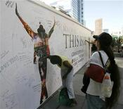 "<p>A woman signs a tribute wall for Michael Jackson at the L.A. Live complex near where people are lining up overnight for the opportunity to purchase tickets for a special showing of the ""Michael Jackson's This Is It"" movie in Los Angeles, California, September 25, 2009. REUTERS/Danny Moloshok</p>"