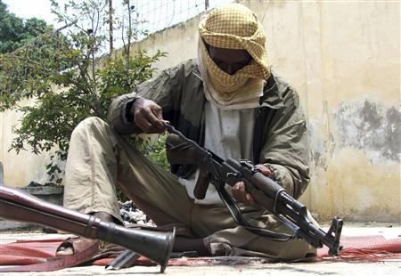 A Somali Islamic militant cleans his weapon at a base in southern Mogadishu, October, 23, 2009. REUTERS/Ismail Taxta