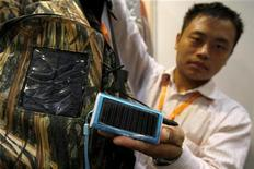 <p>Imagen de archivo de un trabajador de Shenzhen Enon Dynamic Technology Co. posando con un celular solar en una feria de Hong Kong, el 14 de octubre del 2009. REUTERS/Tyrone Siu</p>