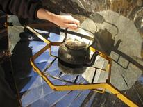 <p>NGO EcoAndina Foundation engineer Christopher Muller places a kettle on a solar cooker in the village of Misa Rumi in Argentina's northern province of Jujuy October 10, 2009. REUTERS/Juan Bustamante</p>