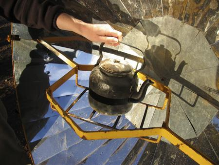 NGO EcoAndina Foundation engineer Christopher Muller places a kettle on a solar cooker in the village of Misa Rumi in Argentina's northern province of Jujuy October 10, 2009. REUTERS/Juan Bustamante