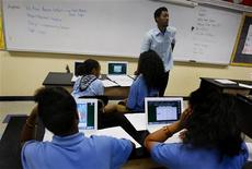 <p>A teacher speaks while his students use their laptops during a class in Dorchester, Massachusetts June 20, 2008. REUTERS/Adam Hunger</p>
