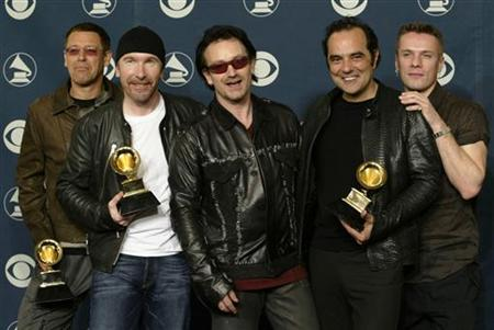 The rock group U2, (L-R) The Edge, Adam Clayton, Bono, producer Daniel Lanois and Larry Mullen, pose after winning five Grammy Awards at the 44th annual Grammy Awards February 27, 2002 in Los Angeles. REUTERS/Mike Blake