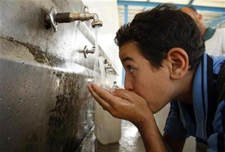 A Palestinian youth drinks water from a public tap in Khan Younis in the southern Gaza Strip October 26, 2009. REUTERS/Ibraheem Abu Mustafa