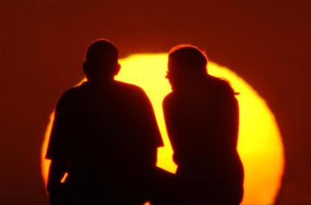 A couple enjoy the spectacular view at Jumeirah beach in Dubai, on December 31, 2002. REUTERS/Anwar Mirza