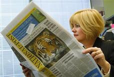 <p>Anne Stone Johnson, Vice President of Weber Shandwick, reads the National Post newspaper in her office in Calgary, Alberta, October 6, 2009. REUTERS/Todd Korol</p>