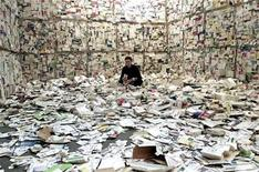 <p>A French artist sits amongst empty medicine boxes inside her creation at Madrid's international contemporary art fair ARCO February 14, 2002. REUTERS/Sergio Perez</p>