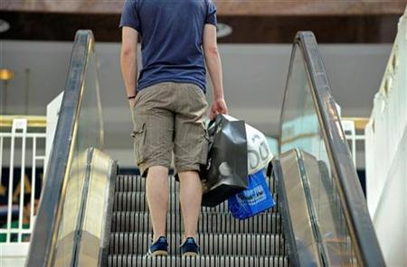 A shopper carrying bags takes the escalator at the Pentagon City Shopping Mall in Arlington, Virginia, September 15, 2009. REUTERS/Mike Theiler