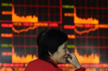 A retail investor monitors share prices in front of an electronic board at a brokerage house in Changzhi, Shanxi province October 30, 2009. REUTERS/Stringer