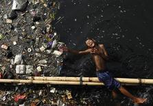 <p>Мальчик играет после школы в грязной реке в Джакарте 5 июня 2009 года. Люди, одержимые навязчивым желанием собирать хлам и складировать его у себя дома, отчасти обязаны подобной манией генам, сообщили британские ученые. REUTERS/Beawiharta</p>