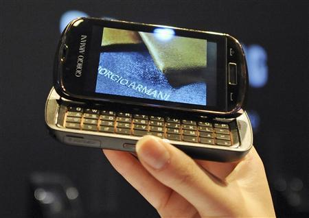 A woman holds an Armani mobile phone during a product launch in Milan October 9, 2009. Italian fashion house Giorgio Armani presented a new 700-euro ($1,032) mobile phone on Friday, a stylish device aimed at complementing the designer's suits. REUTERS/Paolo Bona