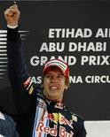 <p>Il pilota della Red Bull Sebastian Vettel celebra la vittoria sul circuito di Abu Dhabi. REUTERS/Steve Crisp</p>