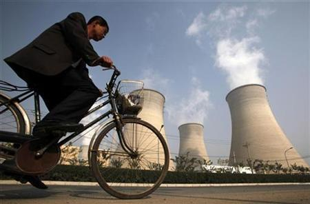 A man rides his bicycle past the chimneys of a power station located on the outskirts of Beijing October 29, 2009. REUTERS/David Gray