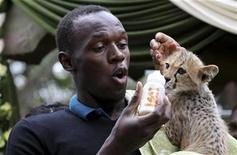 """<p>El velocista jamaicano Usain Bolt junto al cachorro de guepardo que adoptó, en la sede de Servicio de Flora y Fauna de Kenia en Nairobi, 2 nov 2009. El campeón mundial de velocidad y campeón olímpico Usain Bolt adoptó el lunes a un cachorro de guepardo en el Parque Nacional Nairobi de Kenia. El jefe del Servicio de Flora y Fauna de Kenia, Julius Kipng'etich, describió el evento como """"la primera vez en la historia en que el animal más rápido y el hombre más rápido se encontrarán"""". REUTERS/Thomas Mukoya (IMAGENES DEL DIA)</p>"""