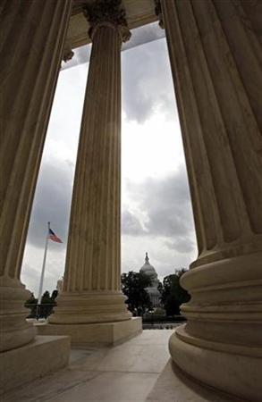 The U.S. Capitol is seen through the pillars of the Supreme Court building in Washington August 6, 2009. REUTERS/Richard Clement