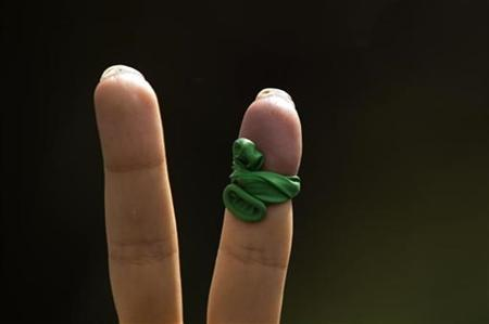 A supporter of defeated presidential candidate and opposition leader Mirhossein Mousavi shows a victory sign with a piece of balloon in the signature colour of his campaign tied on a finger during a rally marking Qods (Jerusalem) Day in Tehran in this September 18, 2009 file photo. REUTERS/Caren Firouz