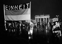 <p>People hold a German flag with the word reading 'Unity' as they cross the newly opened checkpoint between East and West Berlin at the Brandenburg Gate, December 22, 1989. REUTERS/Fabrizio Bensch</p>