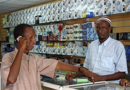 A Somali resident purchases a cell-phone handset at a shopping centre in Mogadishu, November 4, 2009. Somalia's mobile phone business is booming despite the almost daily artillery fire that flies over expensive satellite dishes and the violence that has brought misery to the population of the Horn of Africa nation. REUTERS/Feisal Omar