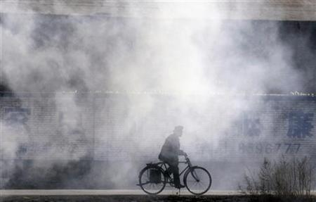 A man rides his bicycle amidst smoke from burning garbage in Ningwu, Shanxi province, December 22, 2007. REUTERS/Reinhard Krause