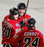 """<p>Игроки хоккейной команды """"Калгари Флеймз"""" Кертис Макэлинни (20) и Крейг Конрой (24) поздравляют Джерома Игинла (в центре) с забитой шайбой в матче против """"Колорадо Эвеланш"""" в Альберте, Канада 28 октября 2009 года. Руководители медицинских служб канадской провинции Альберта заявили в среду, что уволили одного из сотрудников за то, что тот предоставил игрокам Национальной хоккейной лиги возможность преимущественного получения вакцины от вируса гриппа H1N1. REUTERS/Todd Korol</p>"""