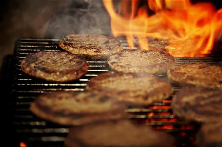 Hamburgers are seen on a barbecue in this undated handout photo. REUTERS/Newscom/Handout