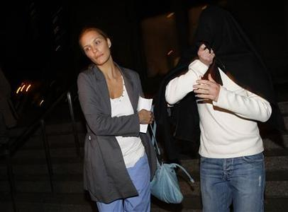 Jason Goldfarb (R) covers his face as he leaves with an unidentified woman from the Manhattan Federal Court house, after being released on bail for his involvement in an alleged insider-trading ring, in New York, November 5, 2009. REUTERS/Brendan McDermid