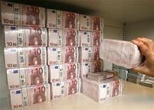 <p>Служащий раскладывает пачки евро номиналом в 10 евро в банке, Вена 21 июля 2009 года. Французская полиция разыскивает водителя-инкассатора, подозреваемого в краже более 10 миллионов евро ($14,85 миллиона). REUTERS/Heinz-Peter Bader</p>