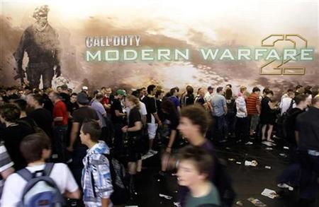 Visitors walk past an exhibition stand for 'Call of Duty - Modern Warfare 2' at the Gamescom 2009 fair in Cologne August 22, 2009. REUTERS/Ina FAssbender
