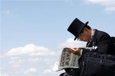 """<p>Человек в ожидании гонки читает газету в Англии 7 июня 2008 года. Британец, скрывающийся от полиции, послал в газету города Суонси собственную фотографию, поскольку ему не понравился снимок, который газета разместила в рубрике """"разыскивается"""". REUTERS/Alessia Pierdomenico</p>"""