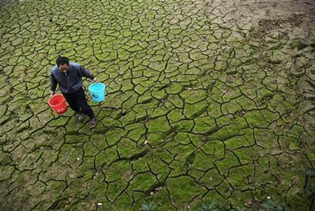 A farmer carries pails to transport water from a partially dried-up pond at the outskirts of Yingtan, Jiangxi province February 5, 2009. REUTERS/Stringer