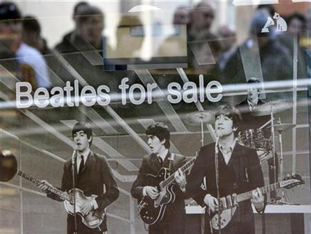 Shoppers are reflected in a window as they queue at a HMV store for the launch of the game ''The Beatles: Rock Band'' in Liverpool, northern England, September 9, 2009. REUTERS/Darren Staples
