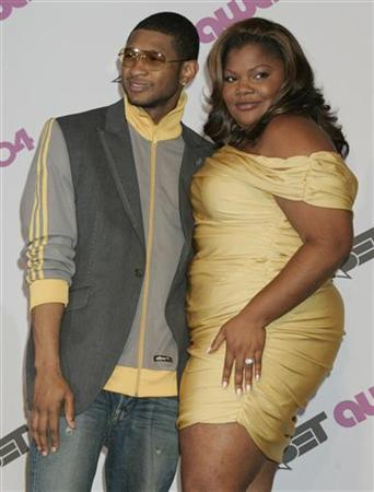 Singer Usher poses with actress Mo'Nique who hosted the Black Entertainment Television award show in Hollywood June 29, 2004. REUTERS/Fred Prouser
