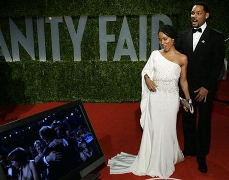 Actors Will Smith and his wife Jada Pinkett Smith look at a television monitor as Danny Boyle wins the Oscar for best director for his work in ''Slumdog Millionaire,'' as they arrive at the 2009 Vanity Fair Oscar Party in West Hollywood, California February 22, 2009. REUTERS/Danny Moloshok