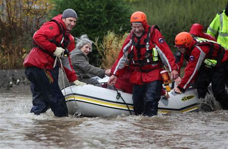 Rescue workers ferry an elderly woman out of flood water in Keswick, northern England, November 19, 2009. REUTERS/Phil Noble
