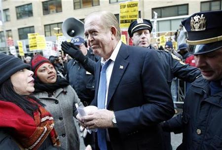 CNN host Lou Dobbs (C) is confronted by protesters (L) and escorted by police during a march on the holiday for slain civil rights leader Martin Luther King Jr. in New York in this January 21, 2008 file photo. REUTERS/Chip East/Files