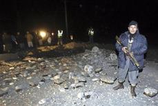 <p>Сотрудник афганской полиции на месте взрыва близ Кабула 20 ноября 2009 года. По меньшей мере 15 человек погибли в результате взрыва, устроенного экстремистом-смертником на юго-западе Афганистана, одной из жертв стал высокопоставленный представитель полиции, сообщили власти страны в пятницу. REUTERS/Omar Sobhani</p>