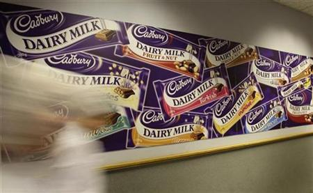 Workers walk past a logo in Cadbury's Bournville factory in Birmingham, central England, October 7, 2008. REUTERS/Darren Staples