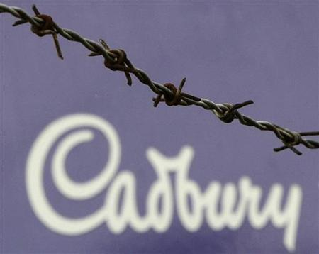 The Cadbury logo is seen behind barbed wire at the company's factory in Bournville, central England, November 9, 2009. REUTERS/Darren Staples