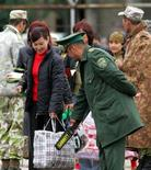 <p>Узбекский таможенник осматривает сумки женщины на пропускном пункте Кара-Су на узбекско-киргизской границе 19 мая 2005 года. Узбекистан без объяснения причин закрыл границу с соседним Казахстаном, сообщил официальный представитель МИД Казахстана Ержан Ашикбаев. REUTERS/Shamil Zhumatov</p>