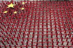 <p>Дети стоят в форме огромного флага КНР в Дэсине 22 сентября 2009 года. Много работы и мало отдыха - норма жизни для большинства детей в Китае, где жесткая конкуренция на рынке труда и амбициозные родители обеспечивают детям долгие часы в компании с книгами, а не с друзьями. REUTERS/China Daily</p>
